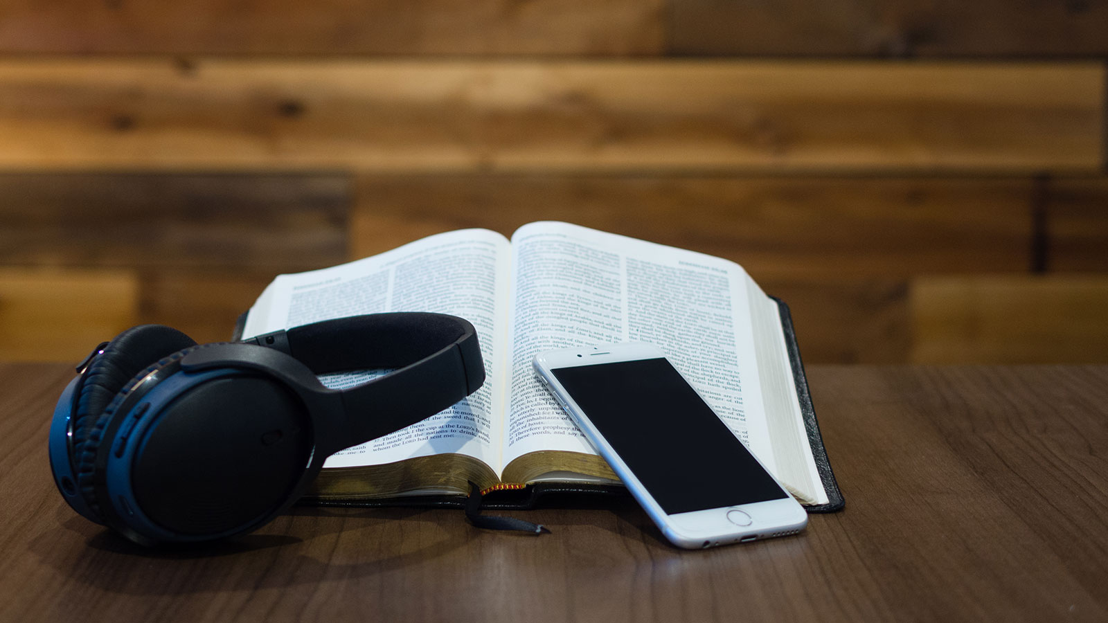 iPhone and headphones laying on an open Bible